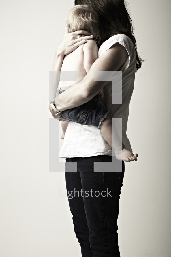A mother and her young baby looking away - isolated on white