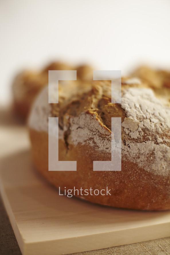 Warm fresh bread sitting on a cutting board.