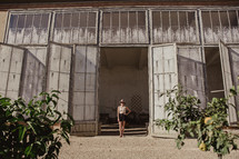 A woman standing in a doorway fig trees in the foreground