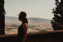 side profile of a woman in a hat with Italian farmland in the background