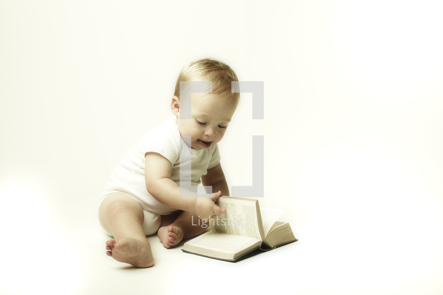 A baby boy flipping through the pages of a bible