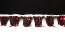 A row of communion cups filled with wine