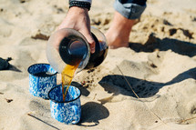 pouring coffee into mugs on a beach