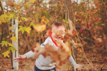 a boy playing in fall leaves