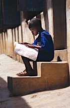 Blind orphan boy sitting on concrete stairs reading a book in Braille