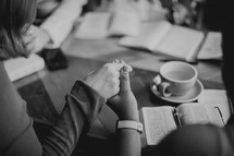 woman's group Bible study holding hands in prayer