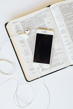 iPhone with earbuds on a Bible