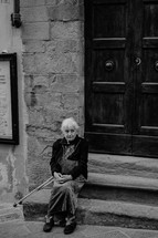 an elderly woman sitting on stone steps outdoors