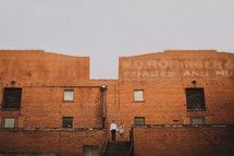 couple standing in front of a brick warehouse building