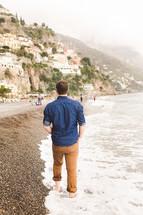 man walking on a beach along an Italian shoreline