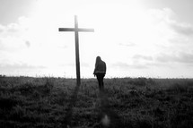 a woman praying in front of a cross