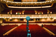 a microphone on stage in an empty auditorium