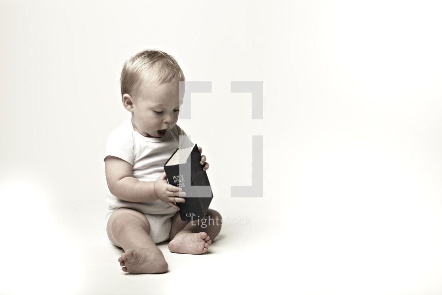 A baby plays with a Bible