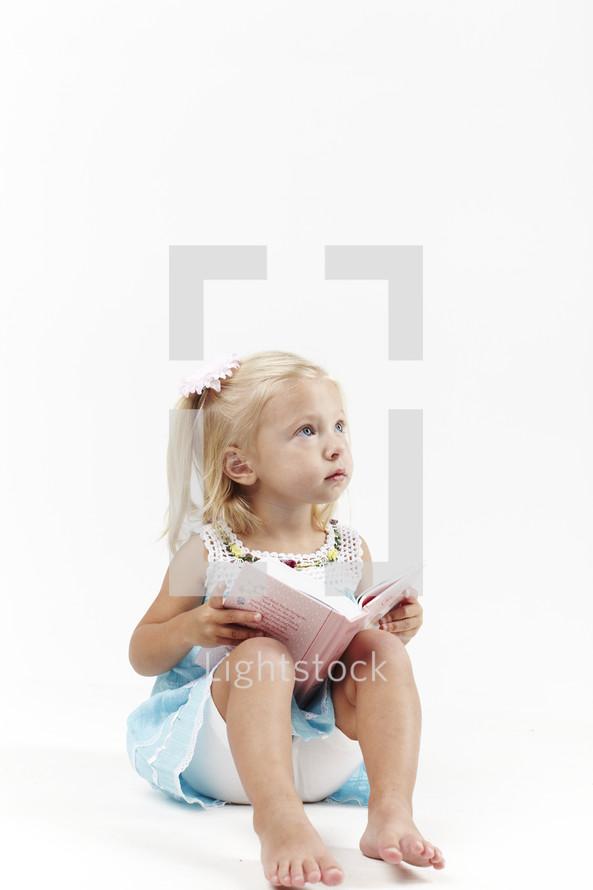 A little girl reads her first children's Bible.