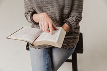 woman sitting on a stool reading a Bible