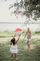 A little girl tosses a beach ball to a young woman.