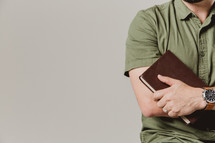torso of a man holding a Bible