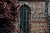 A tall arched window in a brick church.