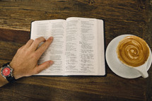 man reading a Bible and a cappuccino