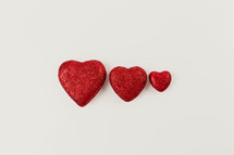 three red hearts on a white background