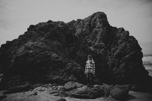 a woman standing on a rock near the ocean