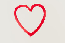 a red painted heart on white paper