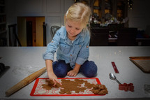 a girl cutting out cookie dough