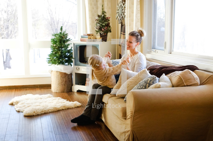 mother and daughter playing on a couch