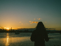 a woman standing on a shore at sunset