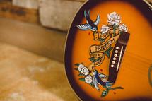 """""""Hope, freedom, faith, love"""" emblem on a guitar."""