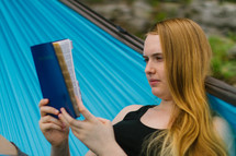 woman reading a Bible on a hammock