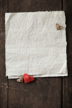wrinkled white paper and heart push pins