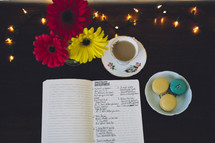 notes in a notebook, gerber daisies, tea, and macaroons