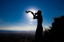 Biblical Character or John the Baptist with a staff in the wilderness blowing the shofar/ rams horn over the city.  Declaring truth and a Voice of calling in the wilderness. Dedicated disciple and biblical character follower of jesus