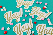 "Small candy hearts and paper cutouts with the word ""yay!"" on an aqua background."