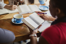 women reading Bibles and taking notes at a Bible study