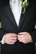 torso of a groom and his boutonniere