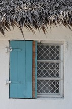 blue shuttered window  of house with thatch roof