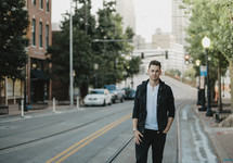 portrait of a man standing on the side of a downtown street