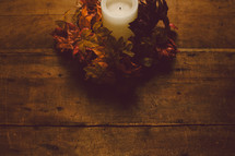 Candle with wreath of fall leaves on a wooden table -- Thanklessness decor.