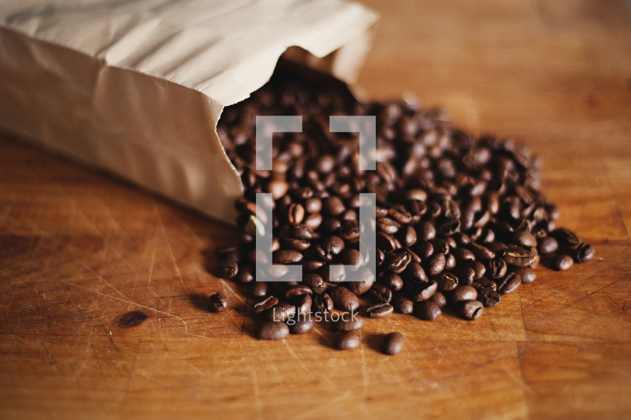 Coffee beans spilling out of a bag on to a wood table.