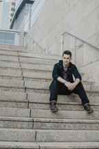 a man sitting on concrete steps