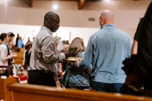 passing around offering trays during a worship service
