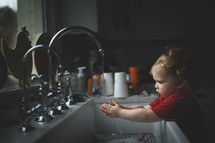 toddler girl playing in water at the kitchen sink