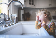 toddler crying by a sink