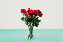 Red roses in a clear glass vase.