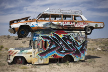 abandoned cars covered with graffiti in a desert