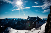 sunburst over jagged snow covered mountains