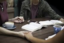 girls holding hands in prayer around a table at a Bible study
