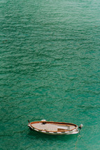 aerial view over a boat on turquoise water